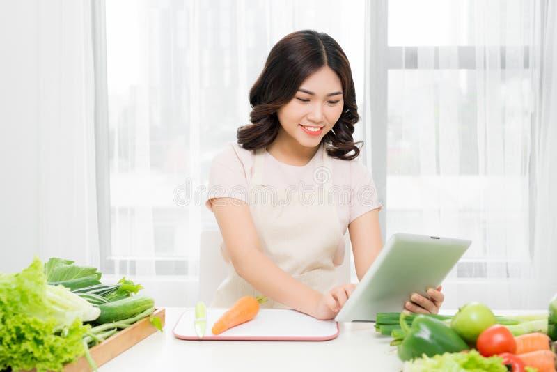 Mujer joven que se coloca en cocina con la tableta, teniendo ide fotografía de archivo libre de regalías