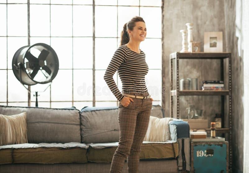 Mujer joven que se coloca en el apartamento del desván foto de archivo libre de regalías