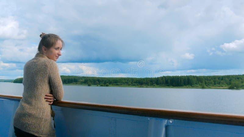 Mujer joven que se coloca en la cubierta del barco de cruceros y que mira el r?o imagen de archivo libre de regalías