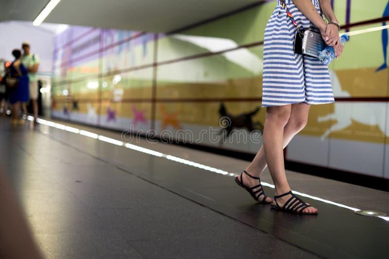 Mujer joven que se coloca en la estación de metro y que espera el tren fotos de archivo