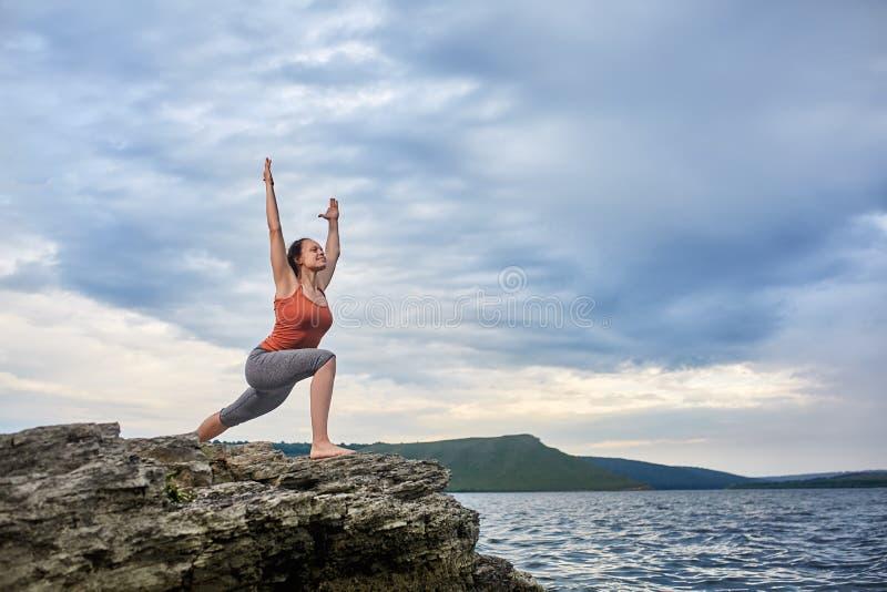 Mujer joven que se coloca en la piedra y la yoga practicante cerca del río grande imágenes de archivo libres de regalías