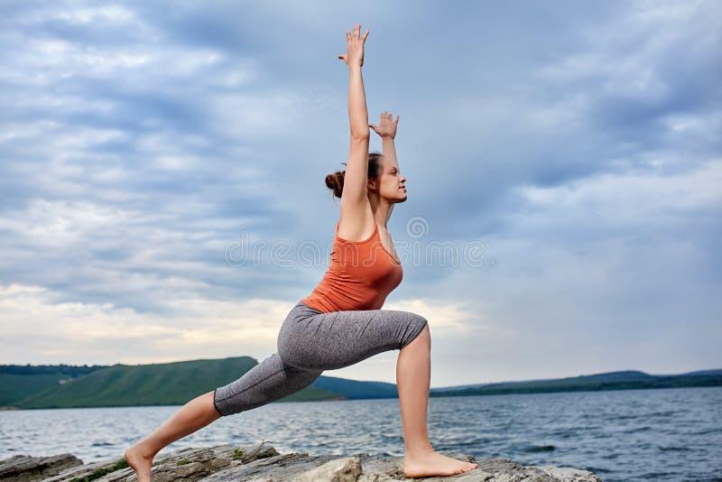 Mujer joven que se coloca en la piedra y la yoga practicante cerca del río grande imagen de archivo