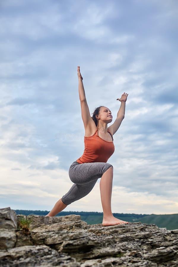 Mujer joven que se coloca en la piedra y la yoga practicante cerca del río grande foto de archivo