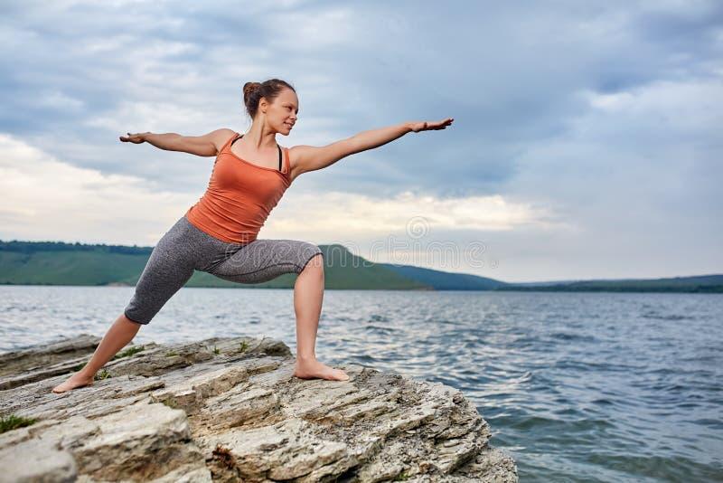 Mujer joven que se coloca en la piedra y la yoga practicante cerca del río grande foto de archivo libre de regalías