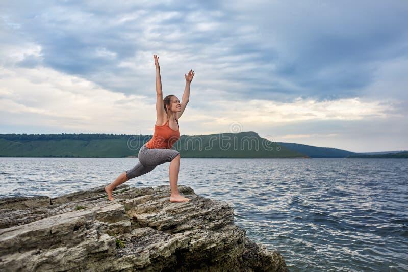 Mujer joven que se coloca en la piedra y la yoga practicante cerca del río grande fotos de archivo