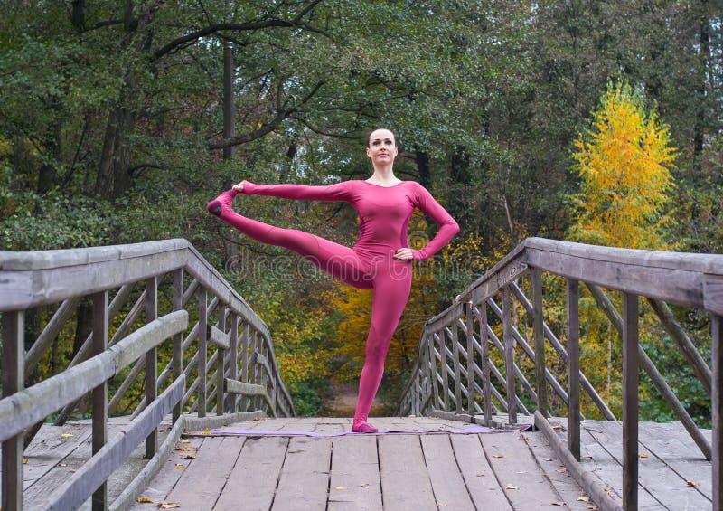 Mujer joven que se coloca en postura de la yoga en el puente de madera en otoño fotos de archivo libres de regalías