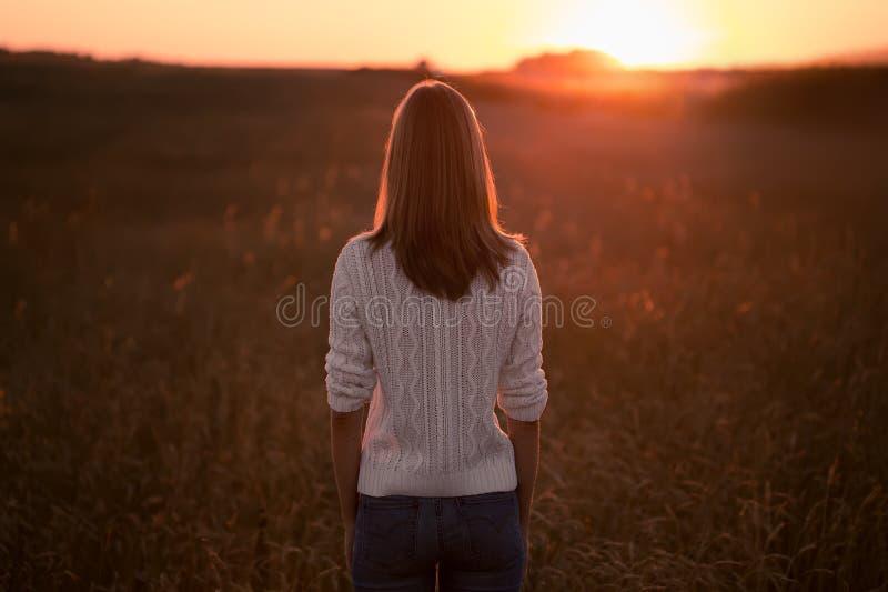Mujer joven que se coloca en un campo de trigo y que mira salida del sol imagenes de archivo