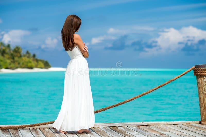 Mujer joven que se coloca en un embarcadero que mira el mar azul hermoso fotos de archivo