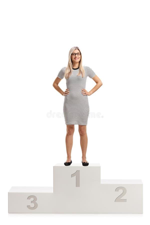 Mujer joven que se coloca en un pedestal y una sonrisa de los ganadores fotos de archivo