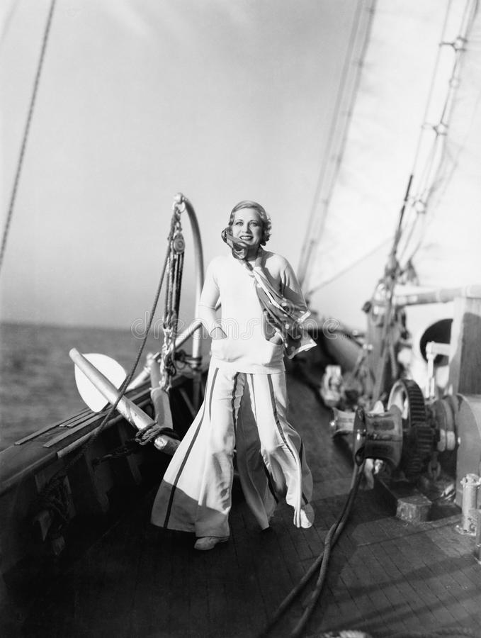 Mujer joven que se coloca en una cubierta de un velero y sonrisa (todas las personas representadas no son vivas más largo y ningú fotografía de archivo