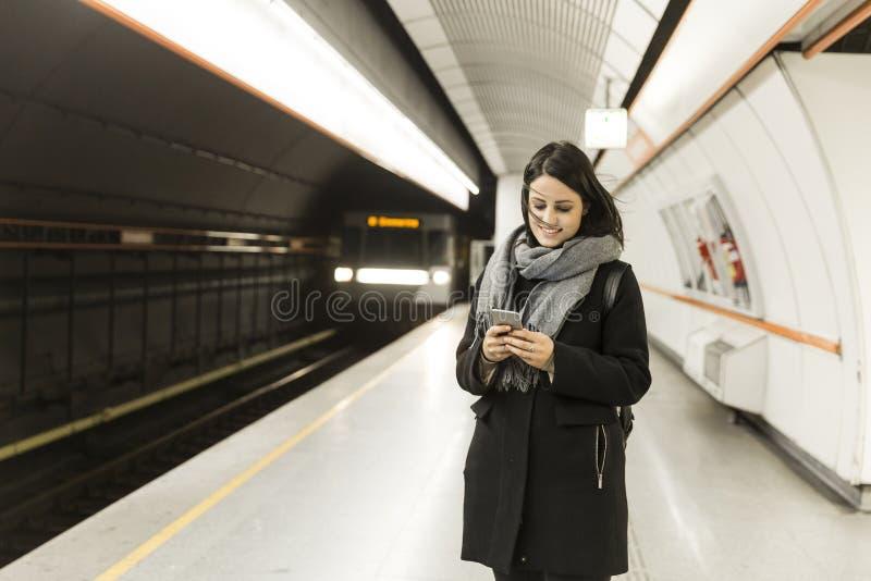 Mujer joven que se coloca en una estación de metro fotografía de archivo libre de regalías