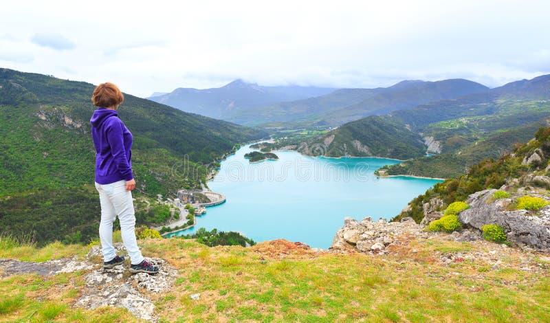 Mujer joven que se coloca en una montaña y que mira un valle imagen de archivo libre de regalías