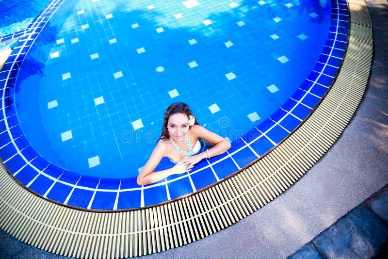 Mujer joven que se coloca en una piscina imagen de archivo