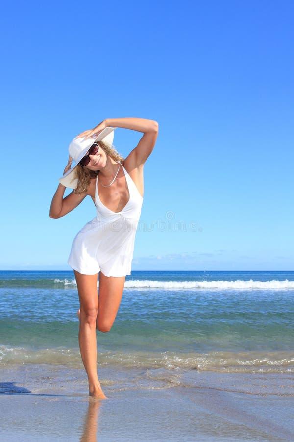 Mujer joven que se coloca en una playa fotografía de archivo