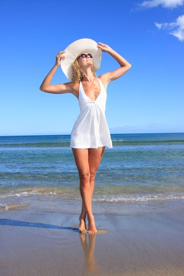 Mujer joven que se coloca en una playa foto de archivo libre de regalías