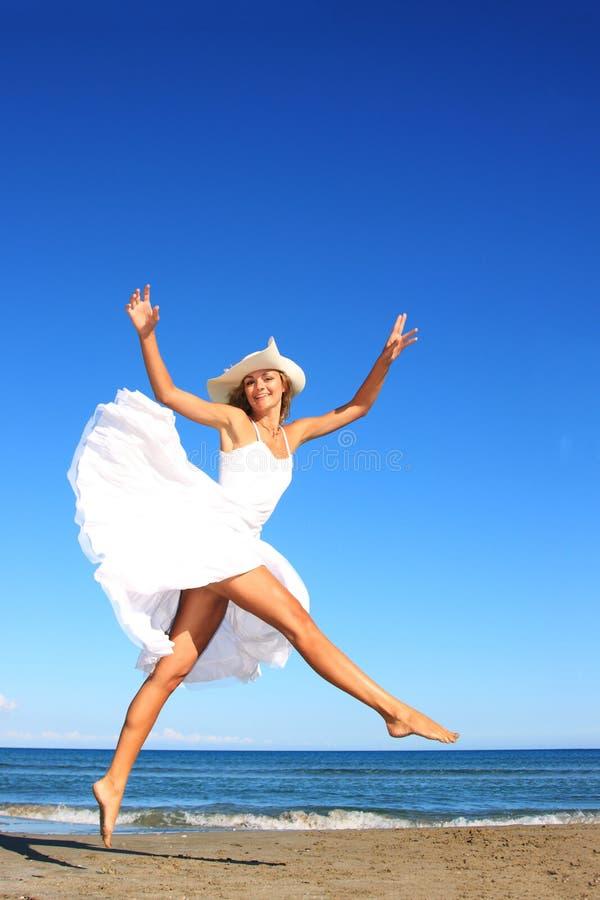 Mujer joven que se coloca en una playa imagen de archivo