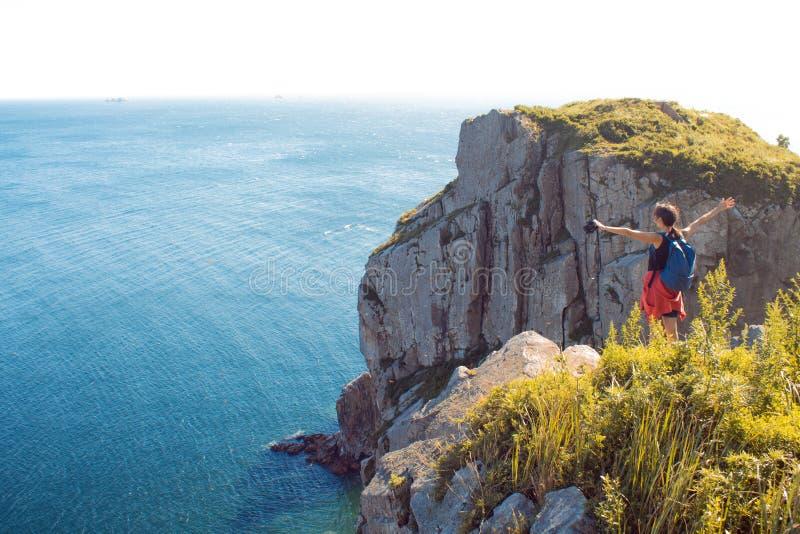 Mujer joven que se coloca solamente en un acantilado rocoso, brazos extendidos Turista de la muchacha en el fondo de la fauna her imagenes de archivo