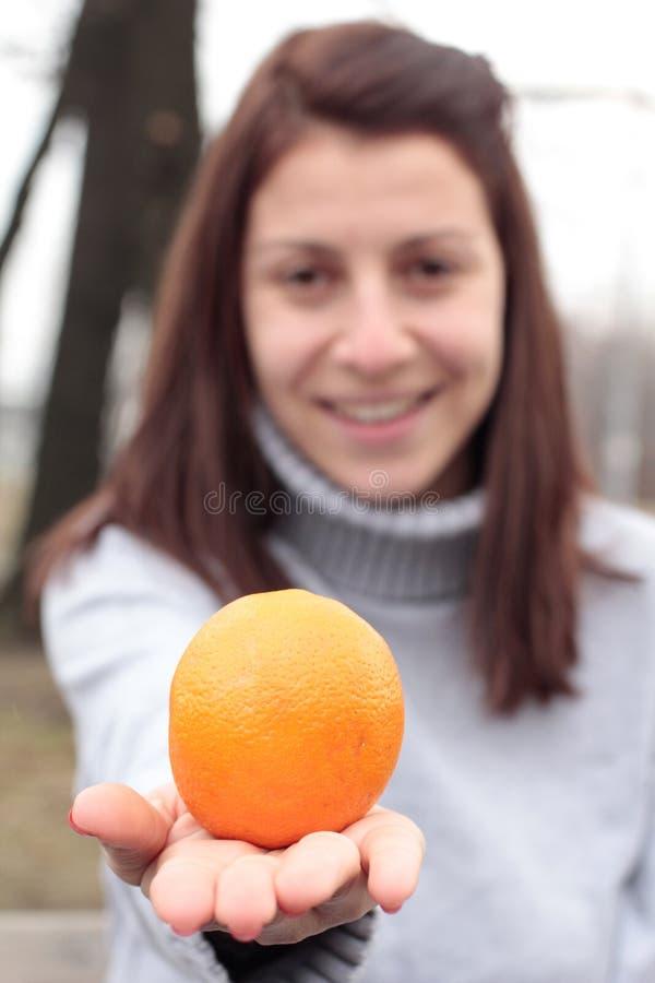 Mujer joven que se considera anaranjada en parque foto de archivo libre de regalías