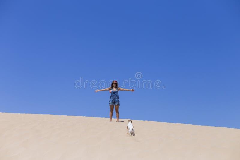 mujer joven que se divierte con su perro en las dunas en el concepto de Portugal, del verano y de la diversión imagen de archivo libre de regalías