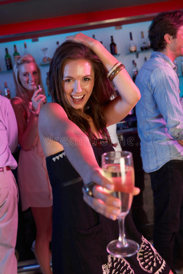 Mujer joven que se divierte en barra ocupada imagen de archivo