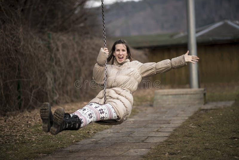 Mujer joven que se divierte en un oscilación foto de archivo