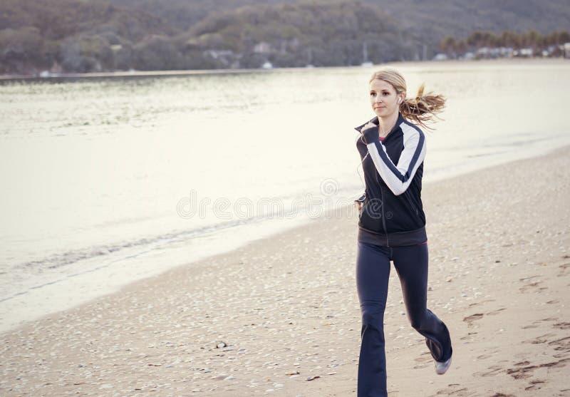 Mujer joven que se ejecuta a lo largo de la playa fotos de archivo