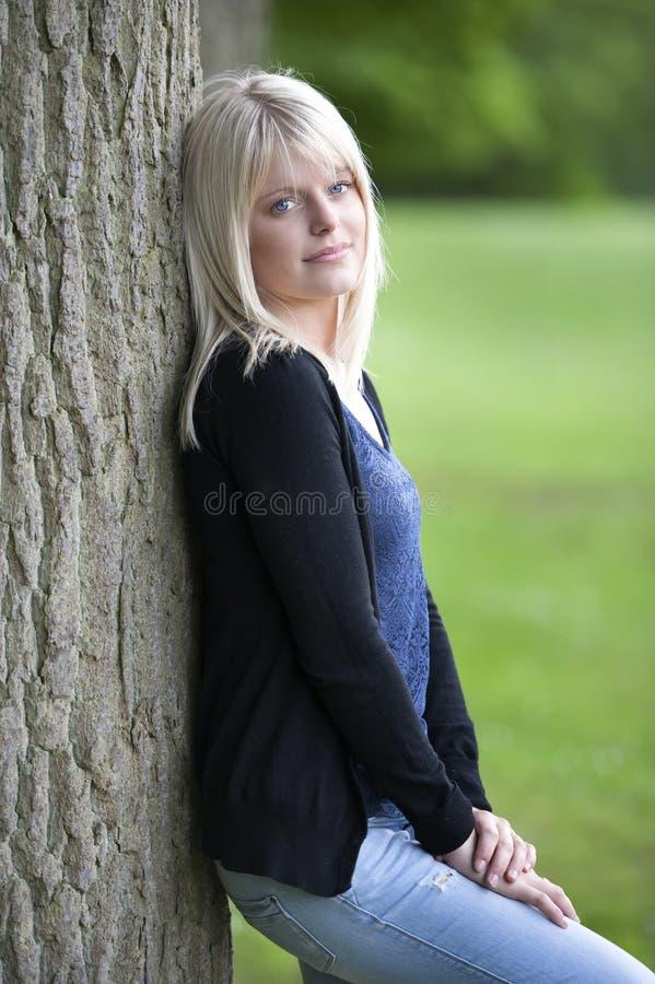 Mujer joven que se inclina contra un árbol fotografía de archivo