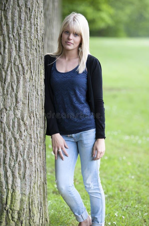 Mujer joven que se inclina contra un árbol foto de archivo