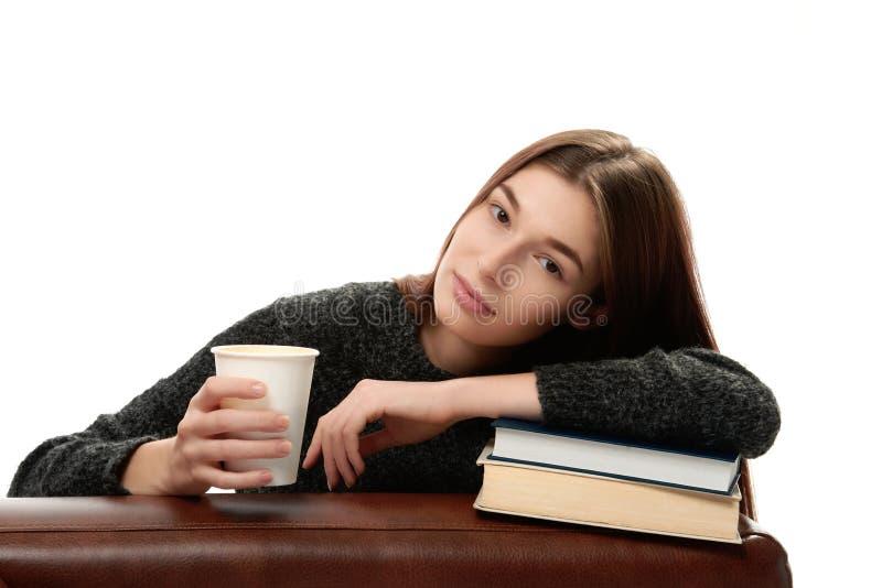 Mujer joven que se inclina en los libros foto de archivo libre de regalías