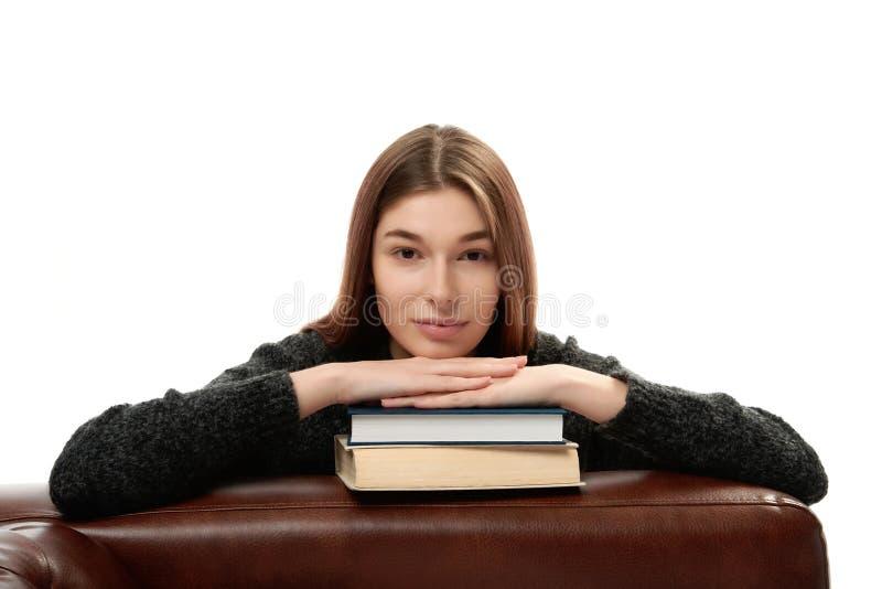 Mujer joven que se inclina en los libros fotos de archivo libres de regalías