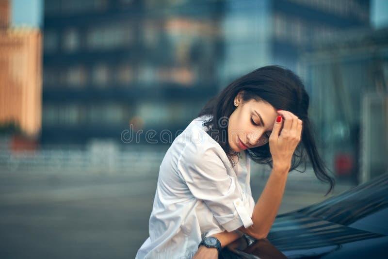 Mujer joven que se inclina en un coche sobre fachada moderna de la oficina imagenes de archivo