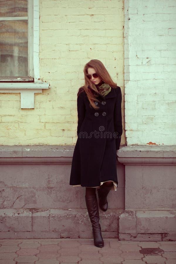 Mujer joven que se inclina en una pared imagenes de archivo
