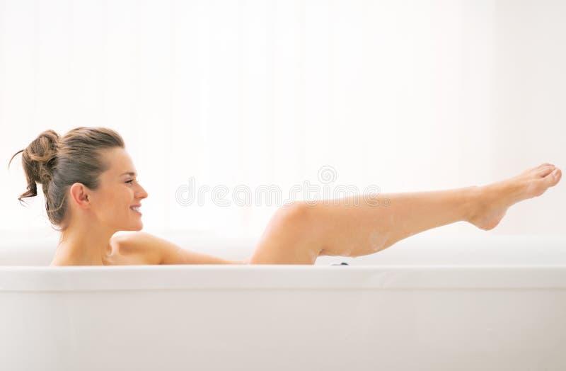 Mujer joven que se lava en bañera imagen de archivo libre de regalías