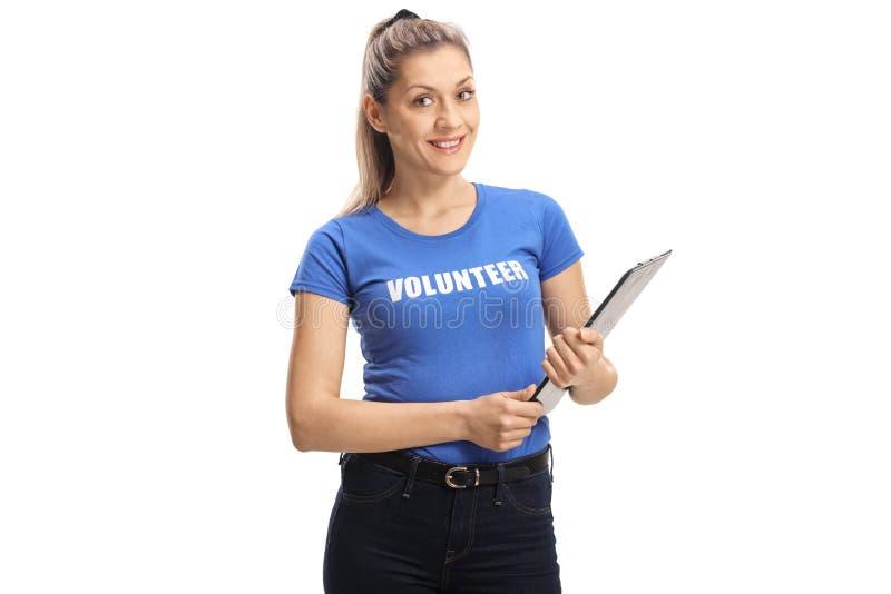 Mujer joven que se ofrece voluntariamente y que sostiene un tablero foto de archivo