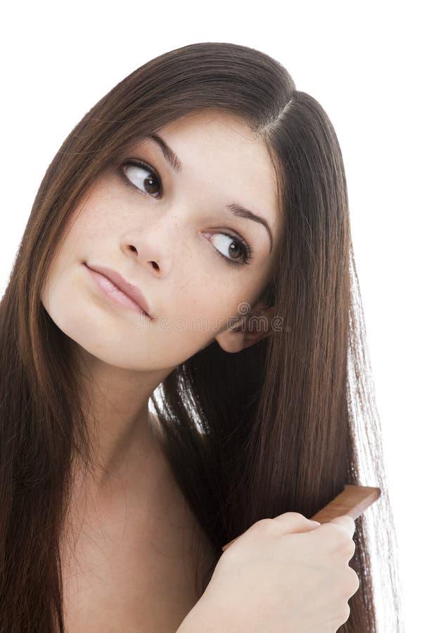 Mujer joven que se peina el pelo imagen de archivo libre de regalías