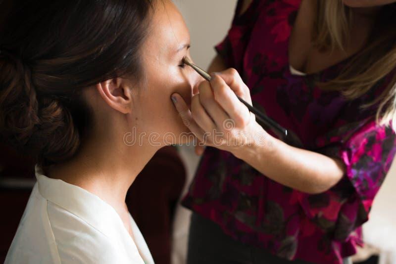 Mujer joven que se prepara para su boda con un artista de maquillaje imagen de archivo