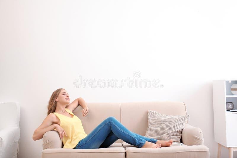 Mujer joven que se relaja debajo del acondicionador de aire foto de archivo libre de regalías