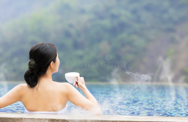 Mujer joven que se relaja en aguas termales fotografía de archivo