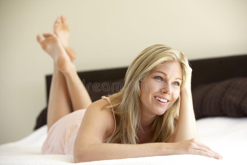 Mujer joven que se relaja en cama foto de archivo libre de regalías