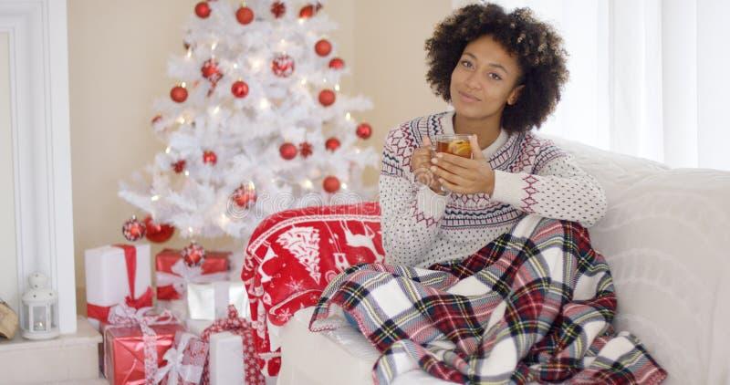 Mujer joven que se relaja en casa sobre la Navidad fotos de archivo