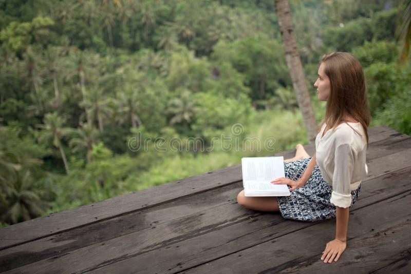 Mujer joven que se relaja en el libro del balcón y de lectura foto de archivo