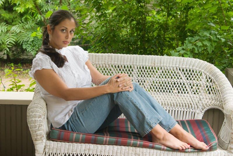 Mujer joven que se relaja en el pórtico fotos de archivo