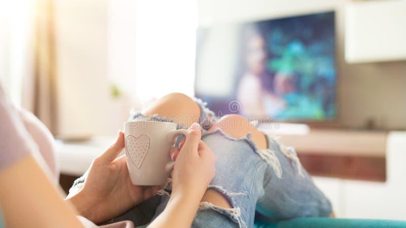 Mujer joven que se relaja en el sofá en casa, viendo la TV y gozando del café, visión superior imágenes de archivo libres de regalías