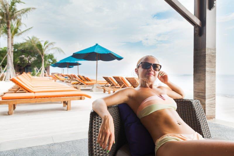 Mujer joven que se relaja en la barra de la playa foto de archivo