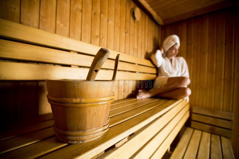 Mujer joven que se relaja en la sauna en el centro del balneario imagen de archivo libre de regalías