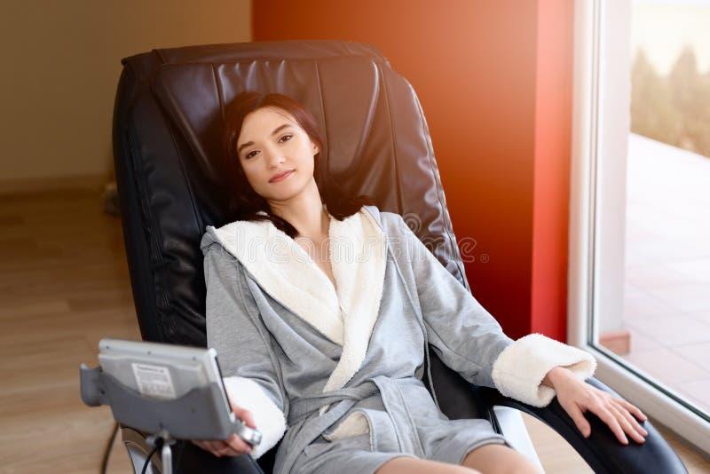 Mujer joven que se relaja en la silla de masaje imagen de archivo