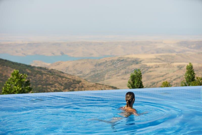 Mujer joven que se relaja en piscina del infinito fotos de archivo