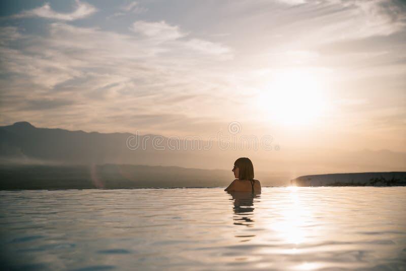mujer joven que se relaja en piscina hermosa en la puesta del sol imagen de archivo libre de regalías