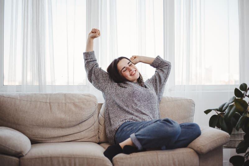 Mujer joven que se relaja en un sofá en sala de estar fotografía de archivo