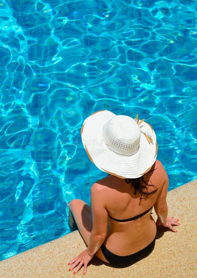 Mujer joven que se relaja por la piscina fotos de archivo